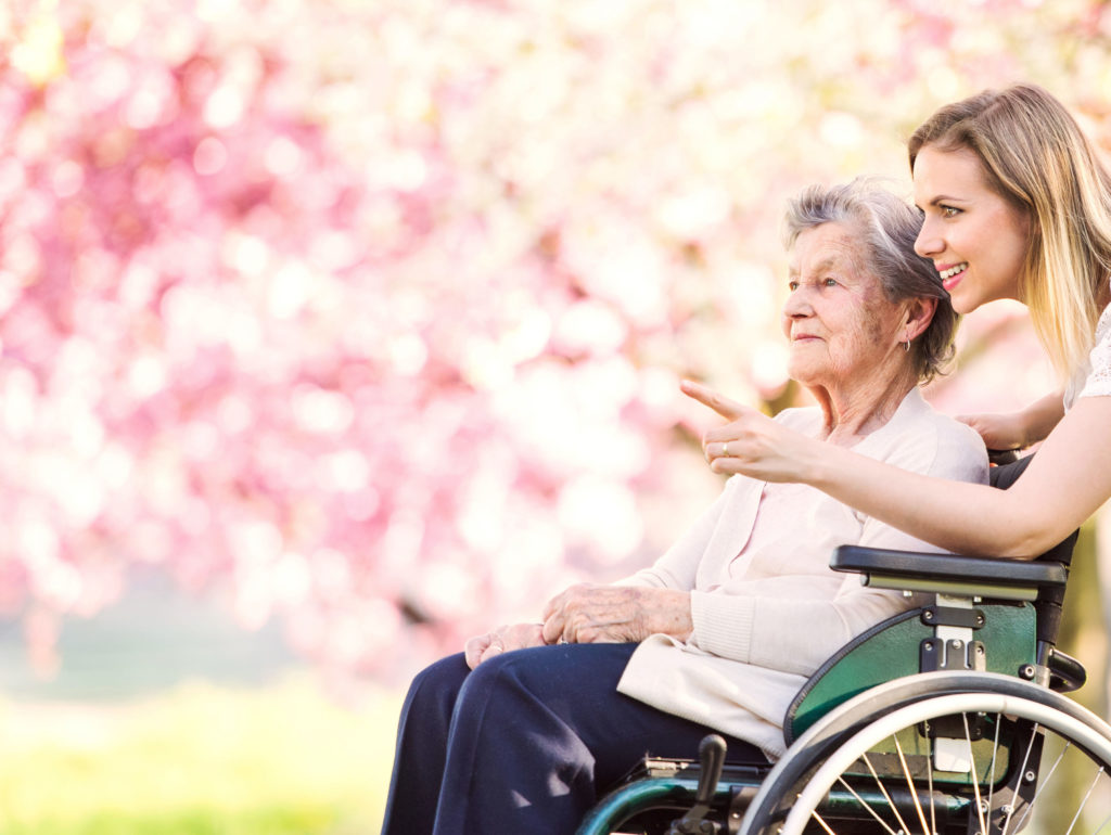 smiling caregiver accompanying elderly woman in a wheelchair