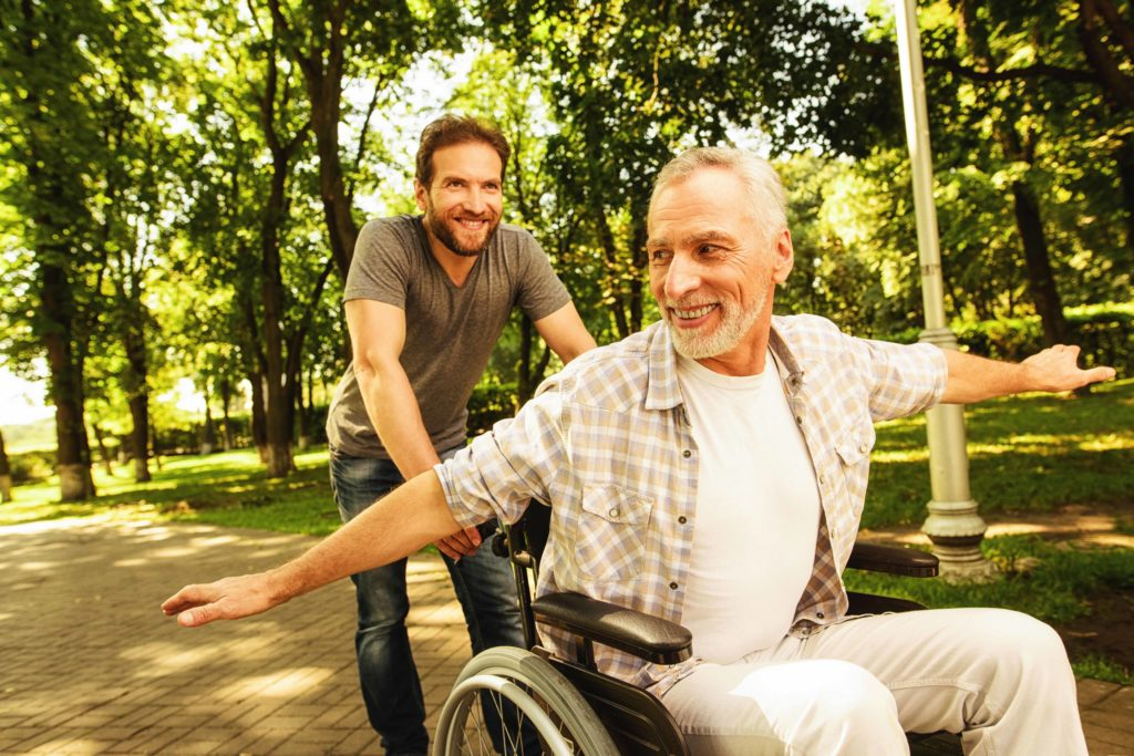 The old man on a wheelchair is walking in the park with his adult son