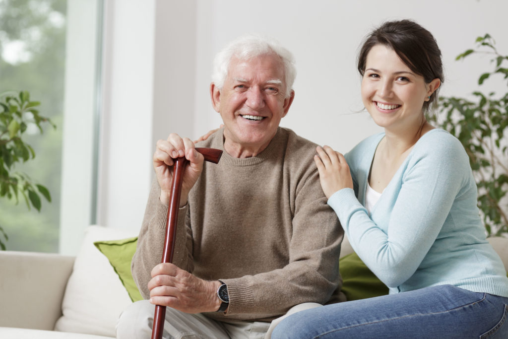 happy elderly man sitting on a coach with a smiling caregiver