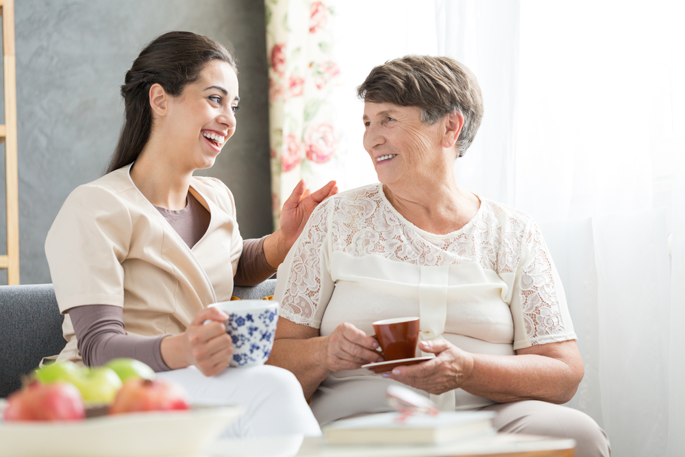 smiling caregiver drinking tea with an elderly woman