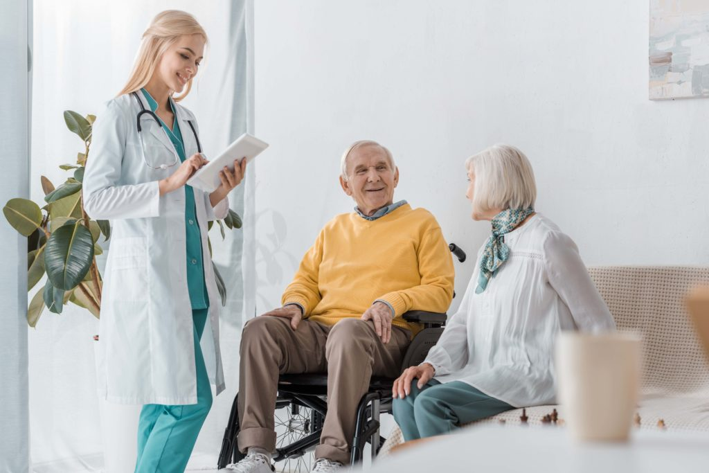 registered nurse talking to elderly man and woman