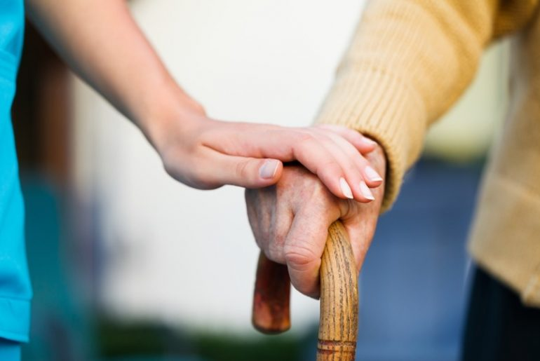 caregiver holding old person hand